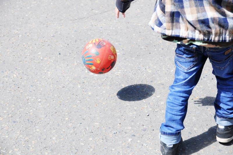Ребенок играя футбол на асфальте, скачку шарика, игрока футбольной команды, тренируя внешний, активный образ жизни стоковое фото rf