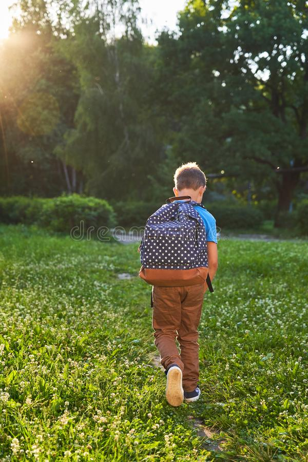 Ребенок идет обучить школьник мальчика идет обучить в утре счастливый ребенок с портфелем на его назад и учебниках внутри стоковая фотография
