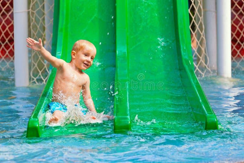 Ребенок имеет потеху в бассейне парка aqua стоковое изображение