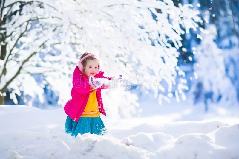 Ребенок имея потеху в парке зимы снежном стоковое изображение