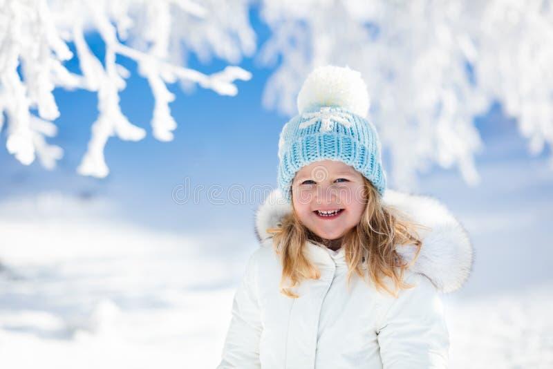 Ребенок имея потеху в снежном парке зимы стоковое фото rf