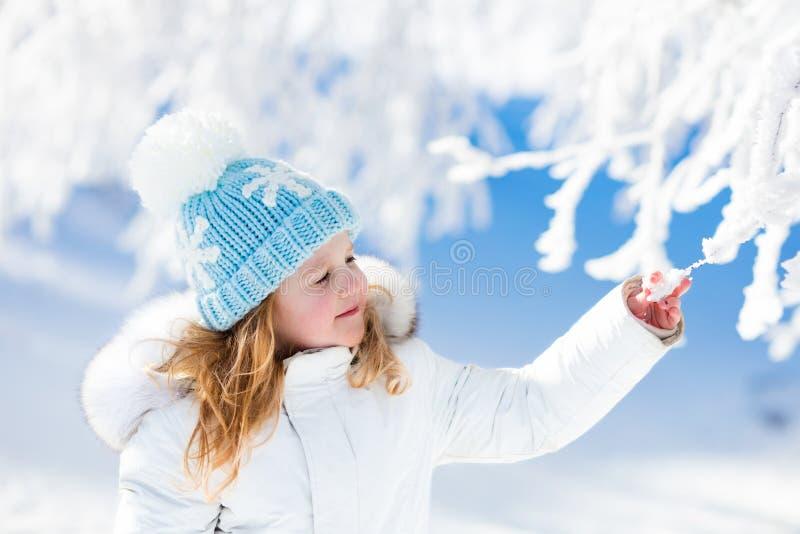 Ребенок имея потеху в снежном парке зимы стоковые фото