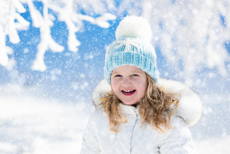 Ребенок имея потеху в снежном парке зимы стоковое изображение rf