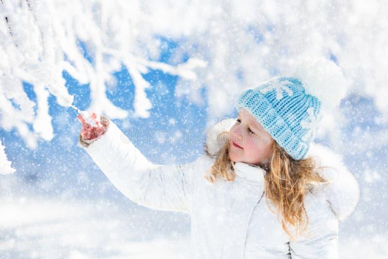 Ребенок имея потеху в снежном парке зимы стоковые изображения