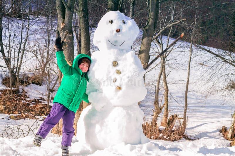 Ребенок имея потеху зимы около снеговика стоковая фотография