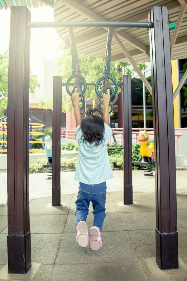 Ребенок имея потеху к висеть на баре в спортивной площадке стоковое изображение