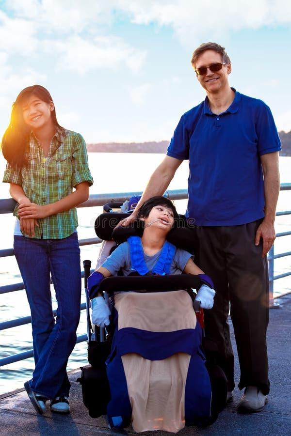 Ребенок-инвалид в кресло-коляске outdoors озером с семьей стоковые фото