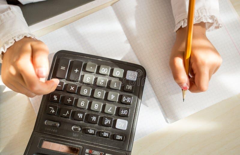 Ребенок используя калькулятор пока делающ домашнюю работу стоковое фото rf