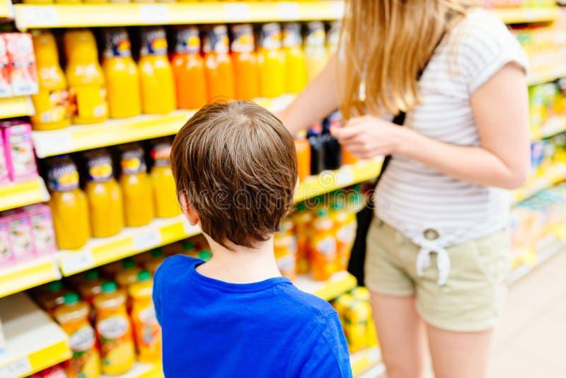 Ребенок и его мать выбирая сок стоковое изображение