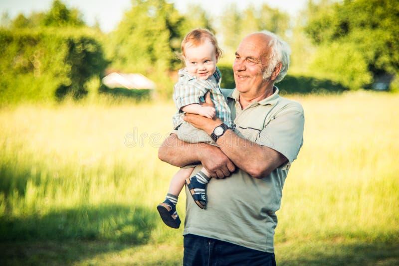 ребенок и его grandpa outdoors стоковое изображение