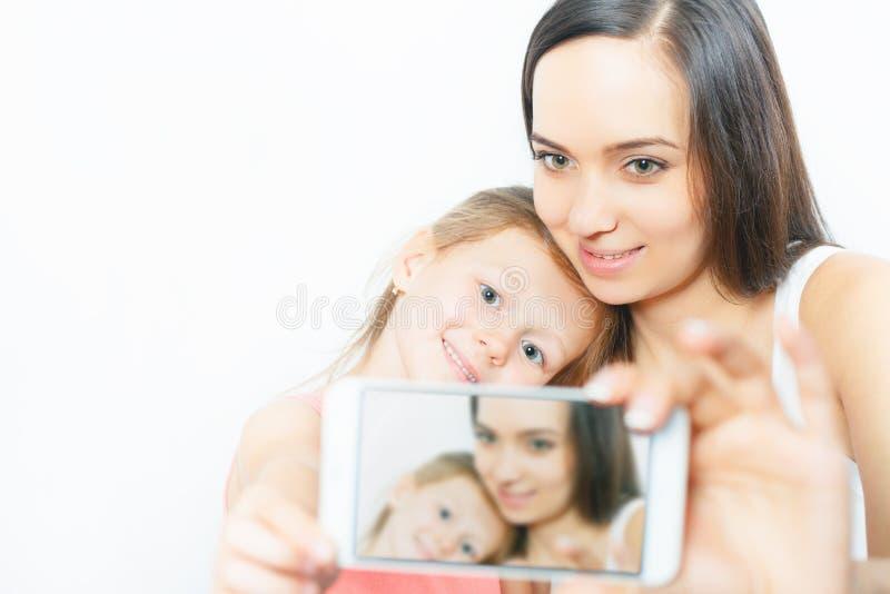 Ребенок и мать делают selfie на мобильном телефоне, хорошей камере стоковая фотография