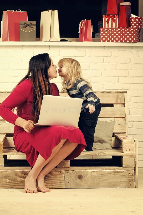 Ребенок и мать рождества счастливые с присутствующими коробкой и компьтер-книжкой стоковое изображение rf