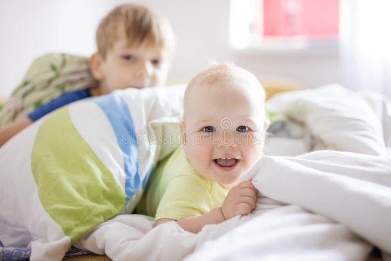 Ребенок и старший брат играя на кровати дома потеха имея отпрысков совместно стоковая фотография rf