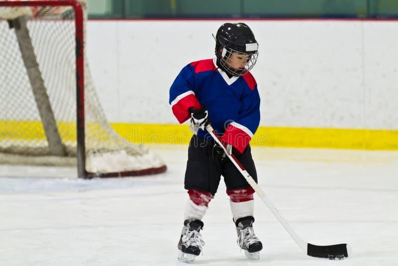 Ребенок катаясь на коньках с шайбой на практике хоккея на льде стоковые изображения rf