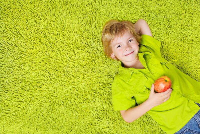 Ребенок лежа на зеленом ковре, держа яблоко стоковая фотография rf