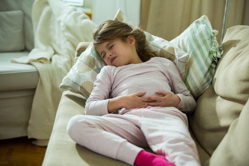 Ребенок лежа на софе в живущей комнате с болью в животе стоковое изображение
