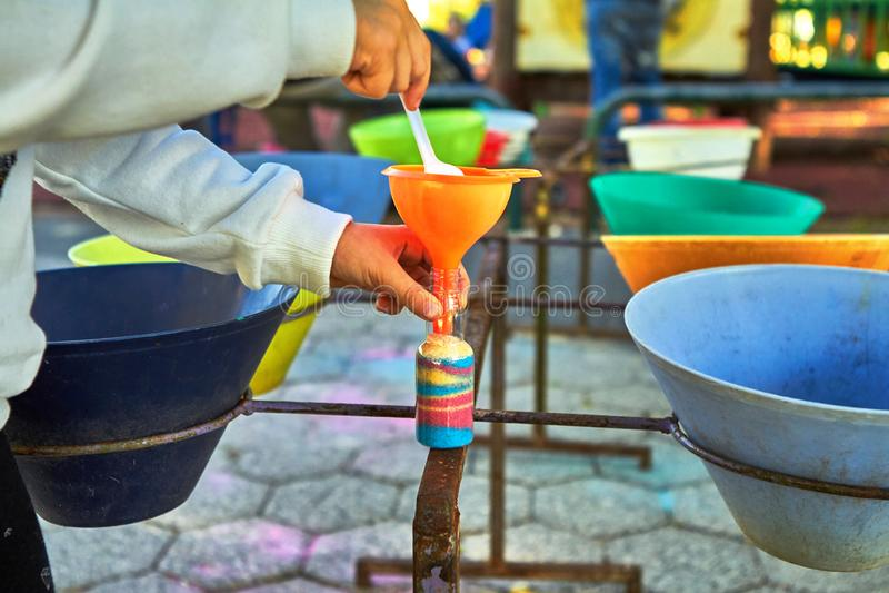 Ребенок льет покрашенный песок в бутылке стоковые фотографии rf