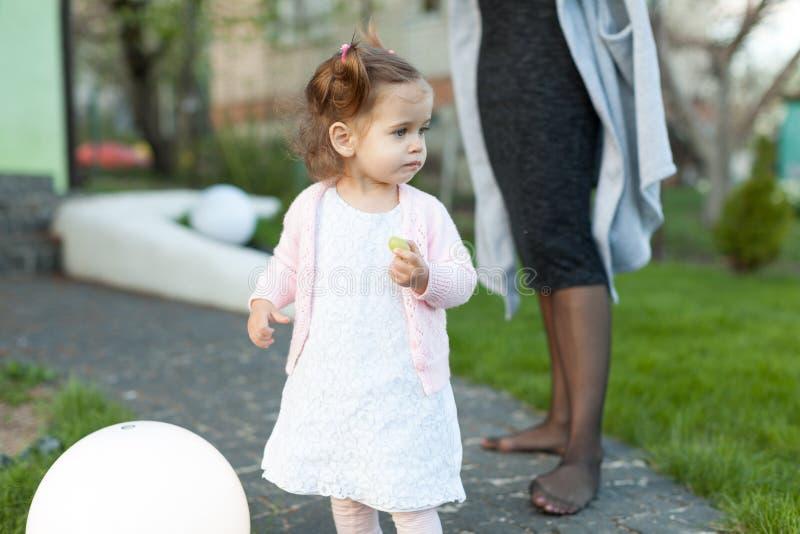 Ребенок маленькой девочки играя на лужайке в задворк с большой электрической лампой стоковое фото rf