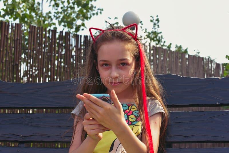 Ребенок маленькой девочки, на голове оправа в форме ушей кота, портрет Девушка с модными красными волосами стоковое изображение