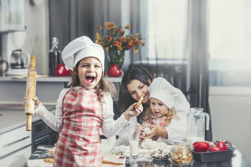Ребенок маленькой девочки с кашеваром матери и сестры счастливым на таблице стоковая фотография rf