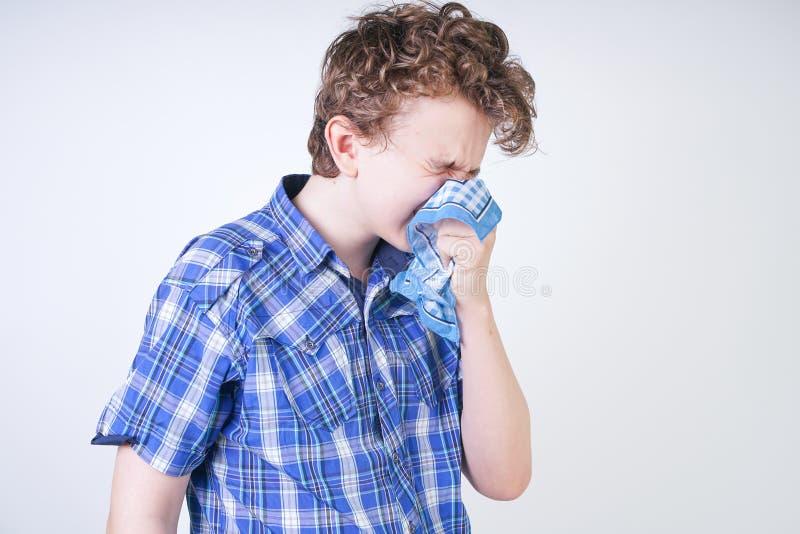 Ребенок мальчика аллергии с жидким носом держа носовой платок Подросток имеет плохое здоровье и стоит на белом al предпосылки сту стоковые изображения rf