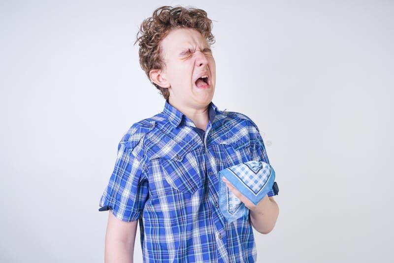 Ребенок мальчика аллергии с жидким носом держа носовой платок Подросток имеет плохое здоровье и стоит на белом al предпосылки сту стоковая фотография rf
