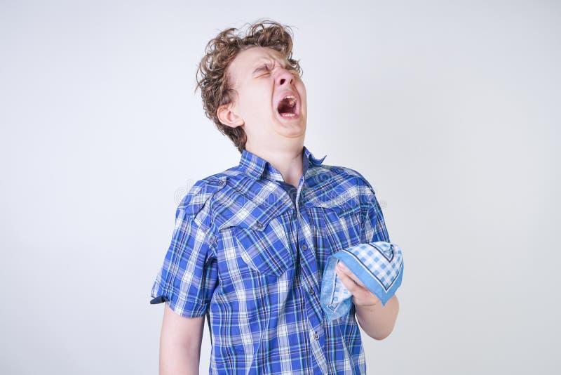 Ребенок мальчика аллергии с жидким носом держа носовой платок Подросток имеет плохое здоровье и стоит на белом al предпосылки сту стоковые изображения