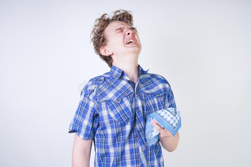 Ребенок мальчика аллергии с жидким носом держа носовой платок Подросток имеет плохое здоровье и стоит на белом al предпосылки сту стоковое фото