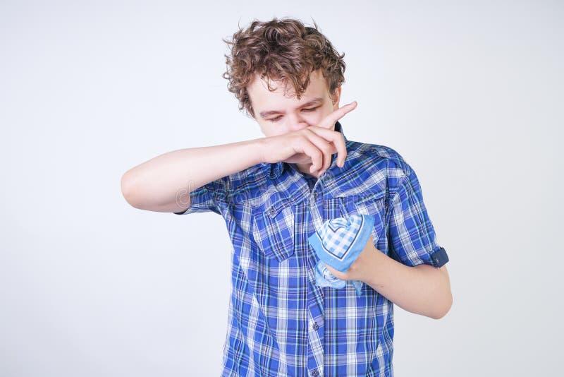 Ребенок мальчика аллергии с жидким носом держа носовой платок Подросток имеет плохое здоровье и стоит на белом al предпосылки сту стоковое изображение rf