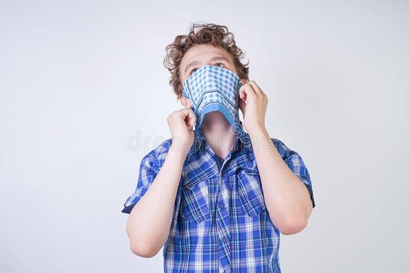 Ребенок мальчика аллергии с жидким носом держа носовой платок Подросток имеет плохое здоровье и стоит на белом al предпосылки сту стоковое фото rf