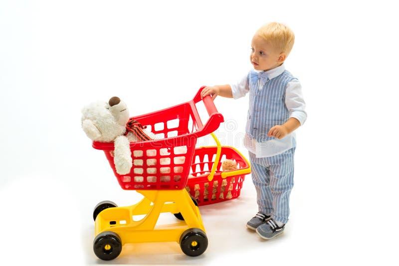Ребенок мальчика в магазине игрушки мальчик идет ходить по магазинам с полной тележкой счастливые детство и забота ходить по мага стоковая фотография rf