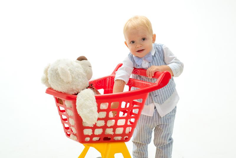 Ребенок мальчика в магазине игрушки мальчик идет ходить по магазинам с полной тележкой сбережения на приобретениях счастливые дет стоковые изображения