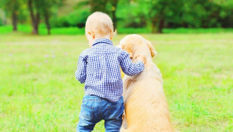 Ребенок мальчика и золотой Retriever выслеживают совместно outdoors стоковое изображение rf