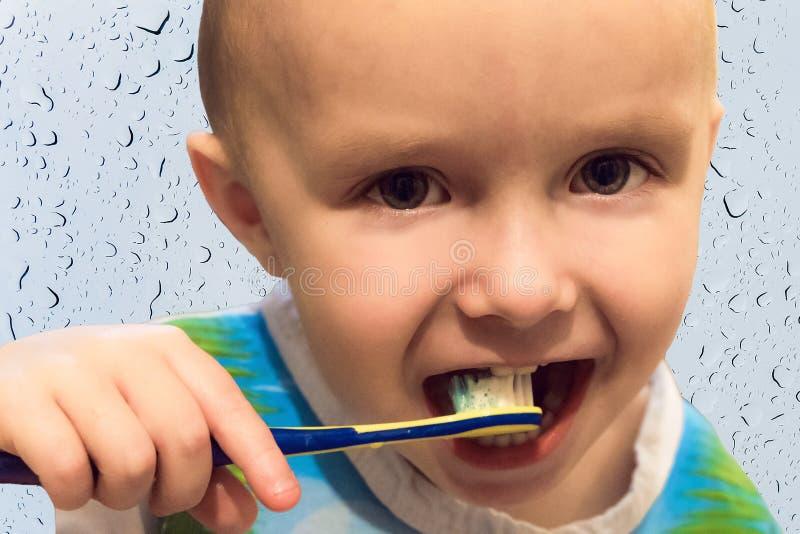 Ребенок мальчика чистя его зубы щеткой с зубной щеткой стоковые фото