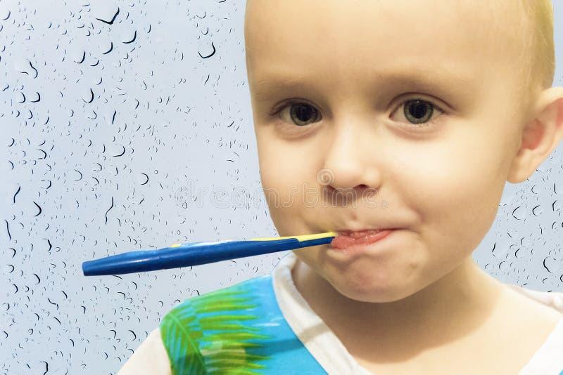 Ребенок мальчика чистя его зубы щеткой с зубной щеткой стоковое фото