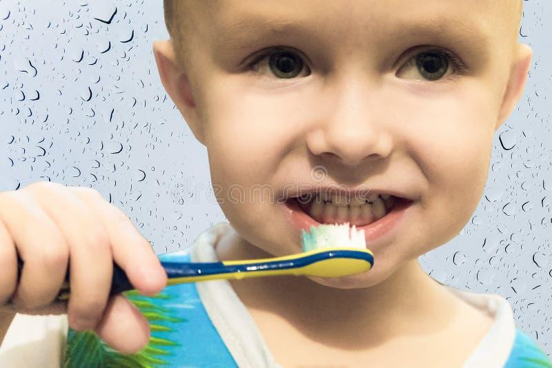 Ребенок мальчика чистя его зубы щеткой с зубной щеткой стоковая фотография rf