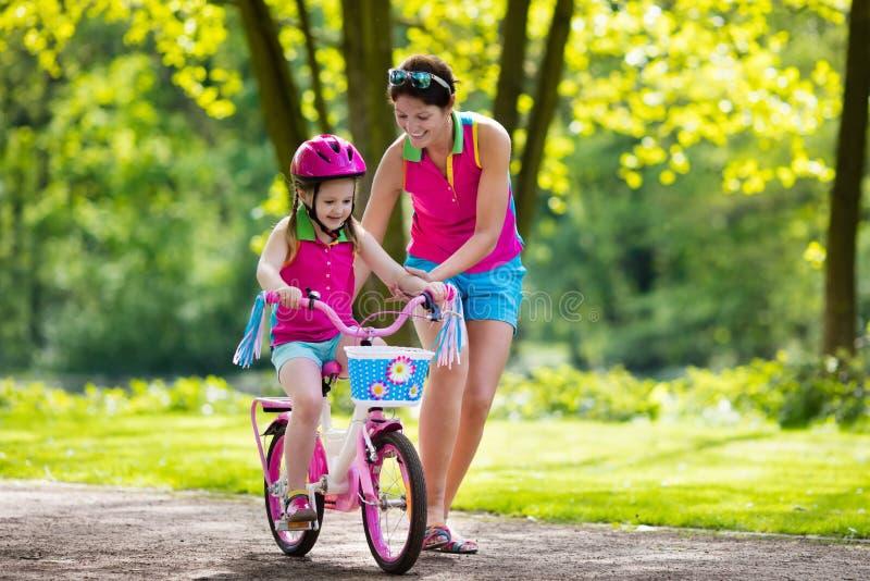 Ребенок матери уча для того чтобы ехать велосипед стоковые фотографии rf