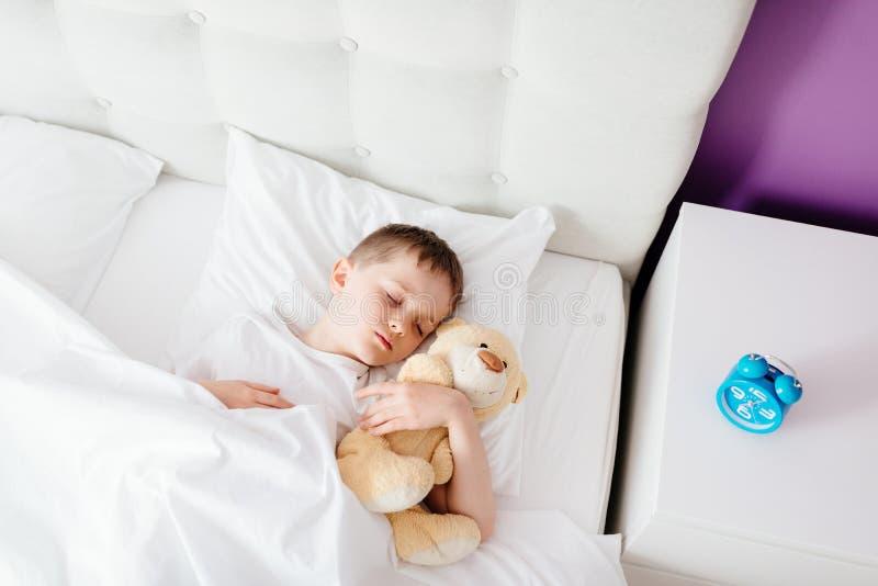 Ребенок мальчика спать в кровати стоковые фотографии rf