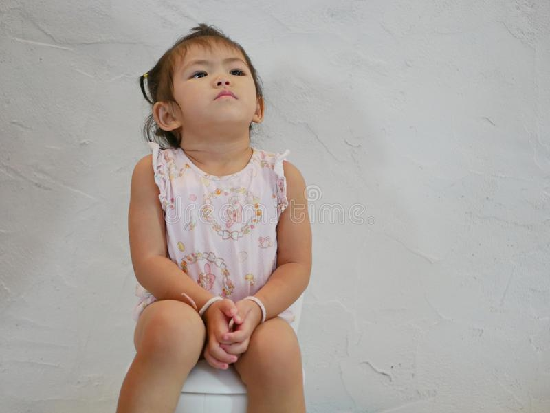 Ребенок 25 месяцев старый азиатский сидя на туалете младенц-размера для тренировки туалета стоковые фото