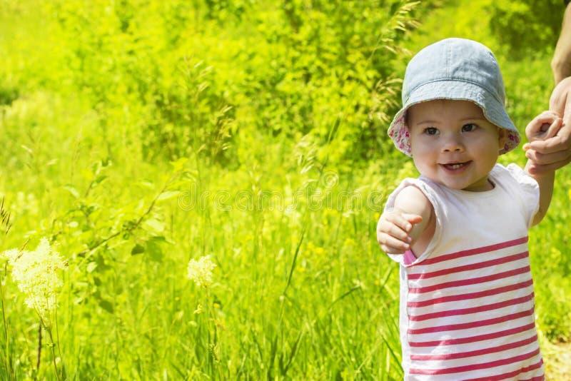 Ребенок 11 месяц идя на зеленый конец-вверх луга Жизнерадостный смеясь ребенок, прогулка лета, портрет стоковая фотография