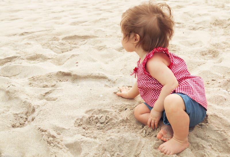 ребенок мечтательный Ребенок маленького ребенка милого темн-с волосами ребенк крошечный сидя на haunches и играя с песком на пляж стоковое фото rf