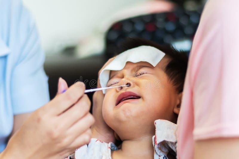 Ребенок младенца испуганный бутона хлопка пользы медсестры для того чтобы собрать соплю маленького ребенка младенца для испытыват стоковые фотографии rf