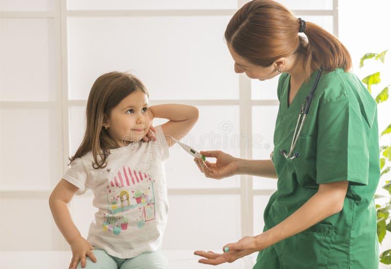 Ребенок молодого женского доктора рассматривая на офисе стоковые изображения