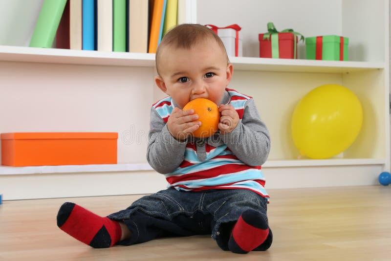Ребенок младенца есть оранжевый плодоовощ стоковая фотография rf