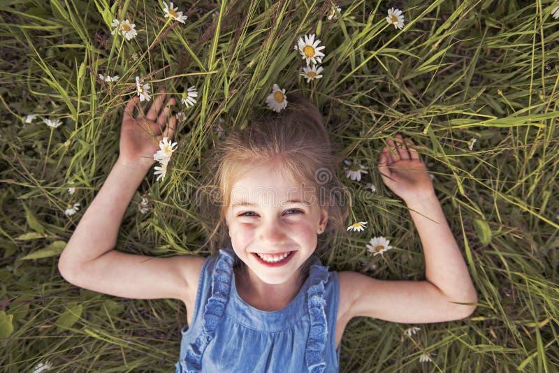 Ребенок на зеленой траве маргаритки во времени захода солнца парка лета стоковая фотография