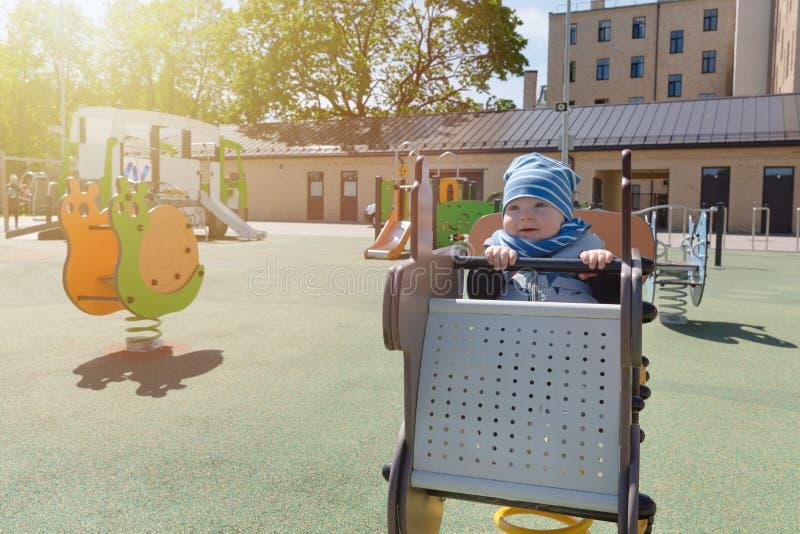 Ребенок на игрушке в спортивной площадке детей стоковое изображение rf