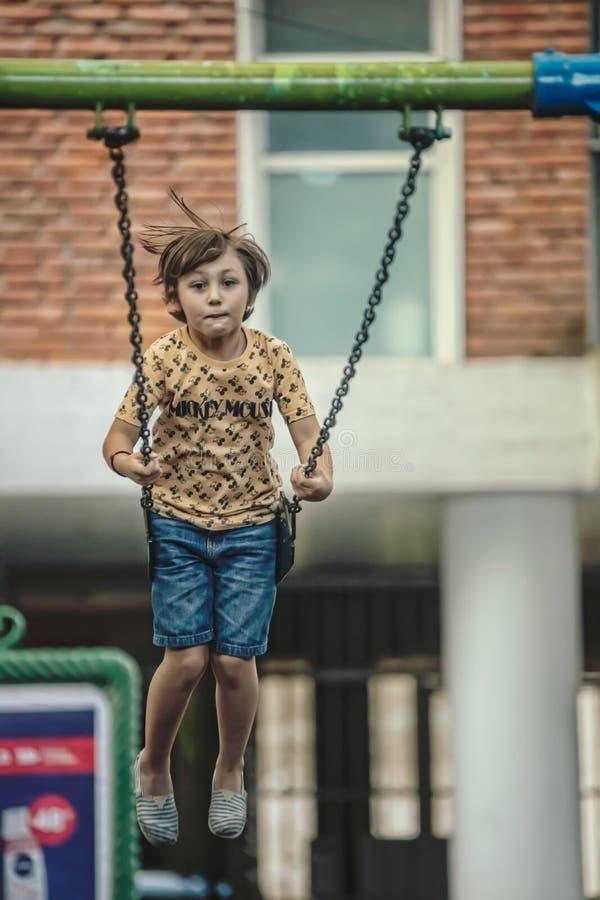 Ребенок на качаниях стоковое фото rf