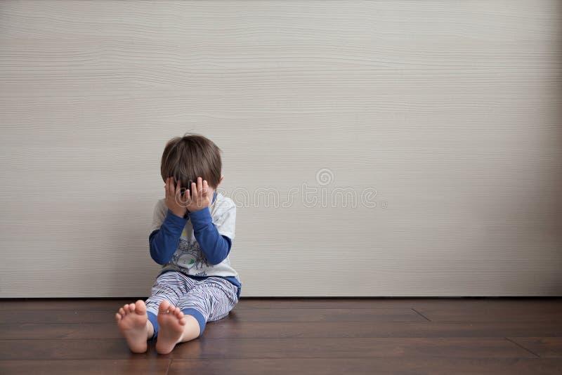 Ребенок на поле плачет и закрывает его сторону с его собственными руками прятать стоковые фотографии rf
