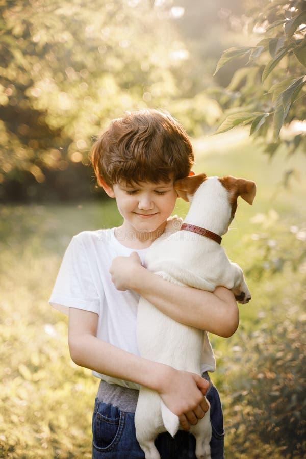 Ребенок обнимая ее друга щенок в outdoors стоковое фото