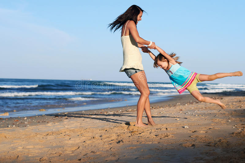Ребенок отбрасывая родительский пляж стоковые фотографии rf